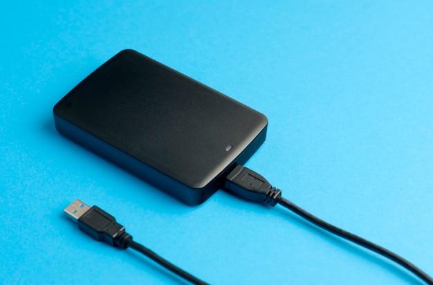 Внешний жесткий диск с кабелем usb на синем столе