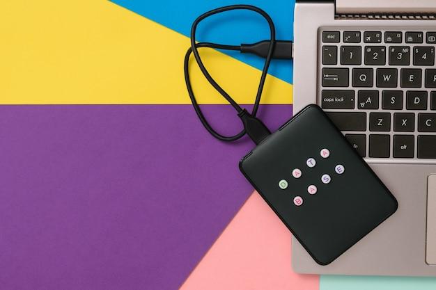 Внешний жесткий диск с ноутбуком на красочном фоне. вид сверху. понятие о резервном хранилище. плоская планировка.