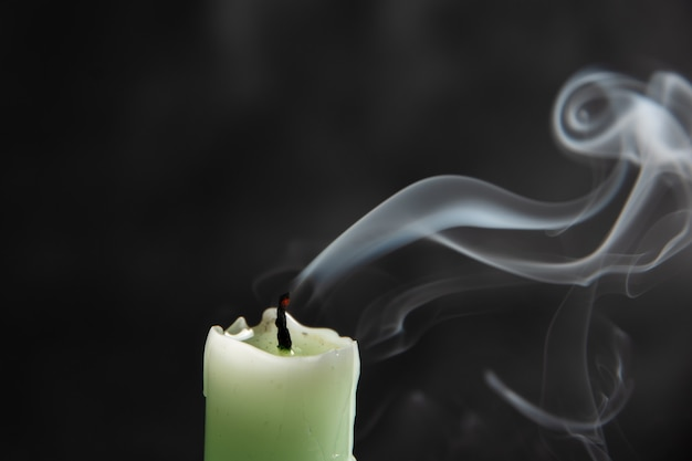 검은 배경, 클로즈업, 추상화에 기발한 모양의 화려한 추상 연기와 함께 소멸된 밝은 녹색 촛불.