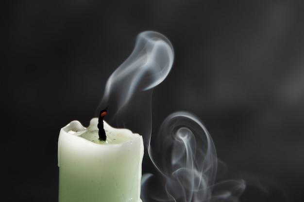 검은 배경, 클로즈업, 추상화에 화려한 추상 연기가 있는 소멸된 밝은 녹색 촛불.