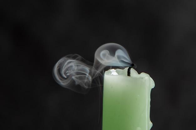 검은 배경에 장엄하고 추상적인 연기가 있는 소멸된 밝은 녹색 촛불.