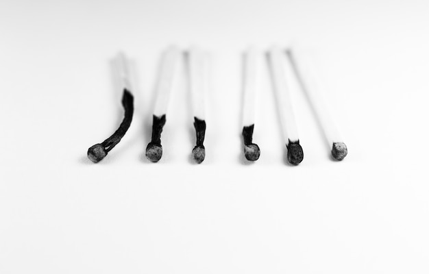 An extinct match in a man's hand. death and aging concept. burned matches in a row on a white background.