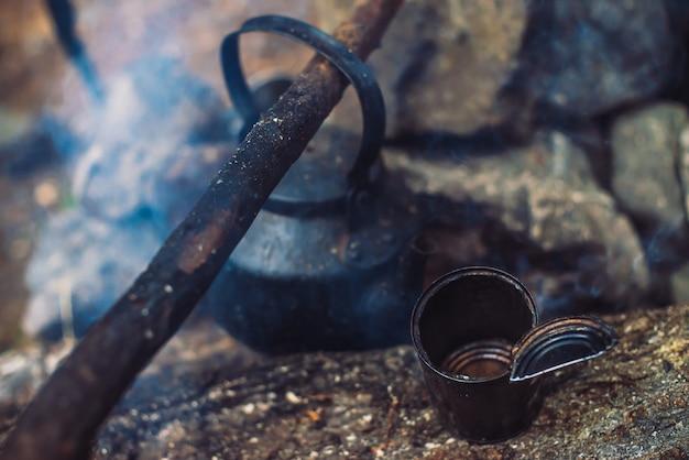 Extinguished bonfire with kettle on large firewood