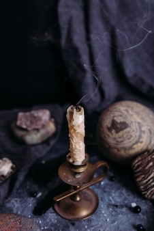 Extinguished candle jug and stones on the witch table