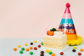 Extinguished candle on cake slice with candies and paper hat