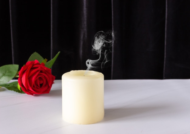 An extinguished candle and a red rose on a black background