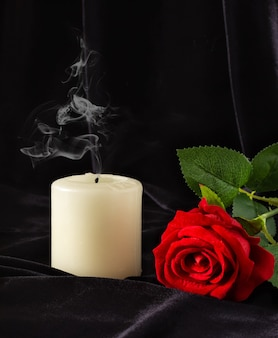 An extinguished candle and a red rose on a black surface