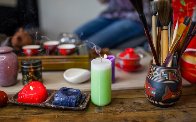 Extinguished candle with smoke in front of tea set on wooden table