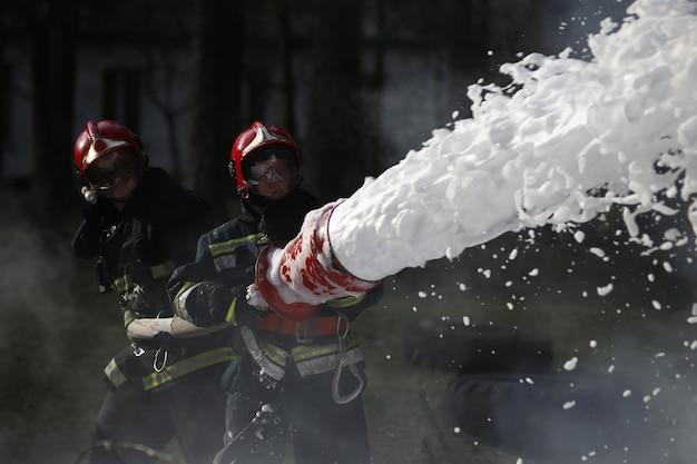 消火する。消防士が働いています。泡を火で満たします。断固たる消防士。火を消してください。