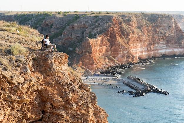 コピースペースのある海岸に座っている超ロングショットの男