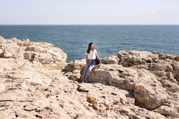 岩の上に座っている超ロングショットの女性