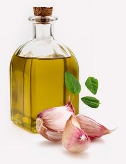 Оливковое масло первого холодного отжима в стеклянной бутылке в деревенском стиле с фиолетовым чесноком и свежими листьями орегано