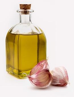 Оливковое масло первого холодного отжима в стеклянной бутылке в деревенском стиле с фиолетовым чесноком