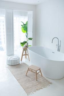 Очень белый и очень светлый минималистичный стильный элегантный интерьер ванной комнаты с современной ванной, зелеными растениями и деревянными элементами.