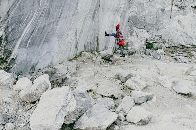 カレリアの青い大理石の抽出。赤い帽子をかぶった赤い鞄を持った女性が大理石の採掘現場に立っています。