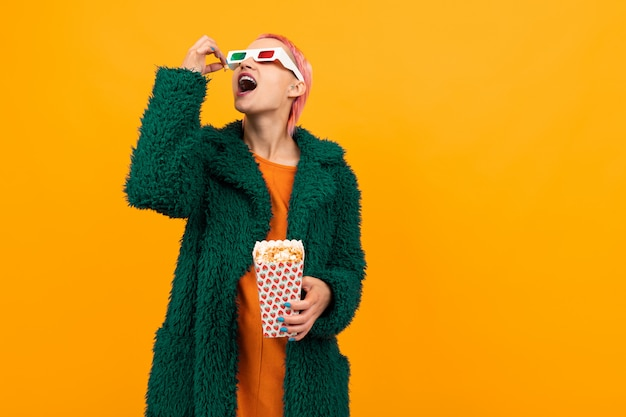 Extraordinary beautiful woman with short pink hair in dark coat and glasses eats popcorn isolated on orange