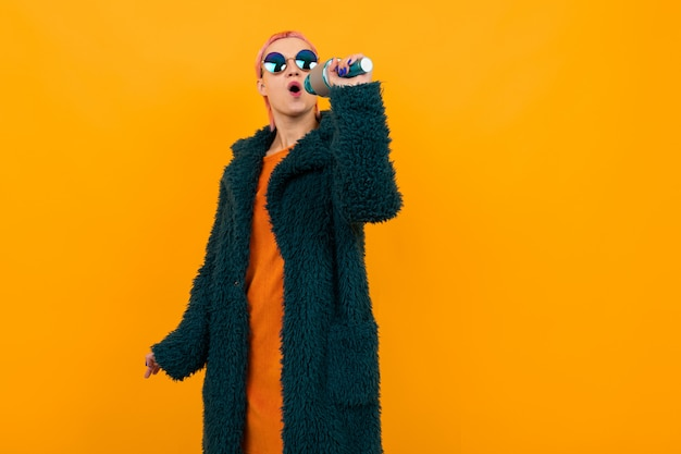 Extraordinary beautiful woman with short pink hair in dark coat and sunglasses sings into a microphone isolated on orange background