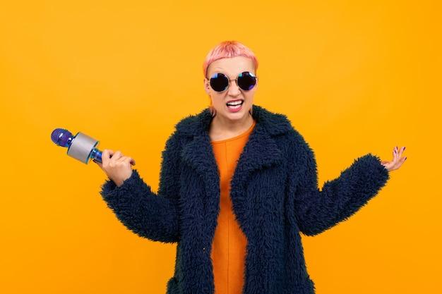 어두운 코트와 선글라스에 짧은 분홍색 머리를 가진 특별한 아름다운 여자는 오렌지 배경에 고립 된 마이크에 노래하고 싶지 않습니다