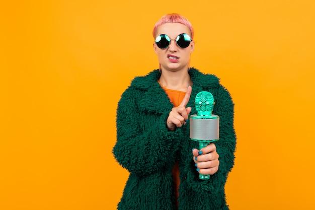 어두운 코트와 선글라스에 짧은 분홍색 머리를 가진 특별한 아름다운 여인은 오렌지에 고립 된 마이크에 노래하고 싶지 않습니다.