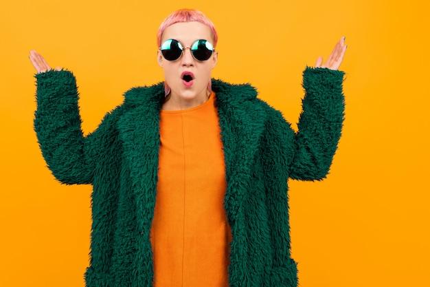 어두운 코트와 선글라스에 짧은 분홍색 머리를 가진 특별한 아름다운 여자는 오렌지에 격리 충격