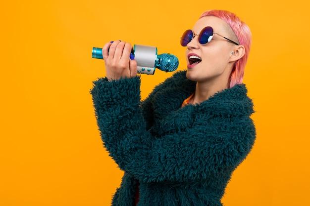 어두운 코트와 선글라스에 짧은 분홍색 머리를 가진 특별한 아름다운 여자가 오렌지 배경에 고립 된 마이크에 노래