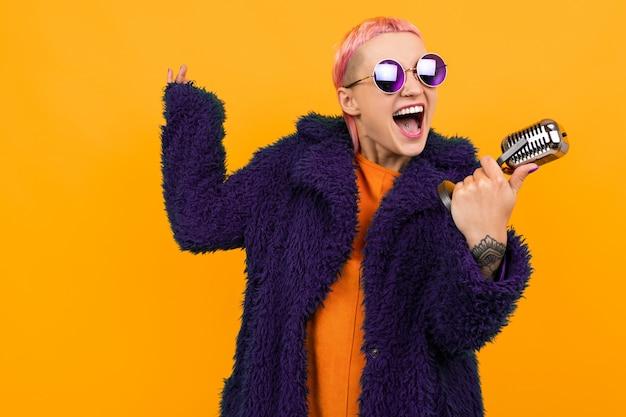 어두운 코트와 선글라스에 짧은 분홍색 머리를 가진 특별한 아름다운 여인은 오렌지에 고립 된 마이크에 노래