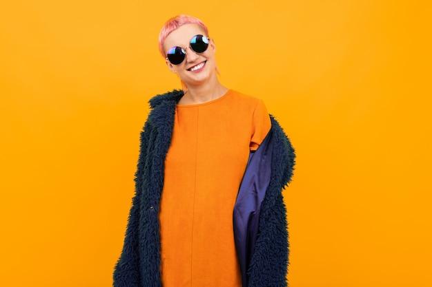 어두운 코트와 선글라스에 짧은 분홍색 머리를 가진 특별한 아름다운 여인이 오렌지에 고립 된 미소