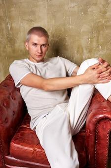 革のソファでポーズをとる流行の服を着た非常に自信のある若い男は、足を後ろに投げてソファに自由に座っています