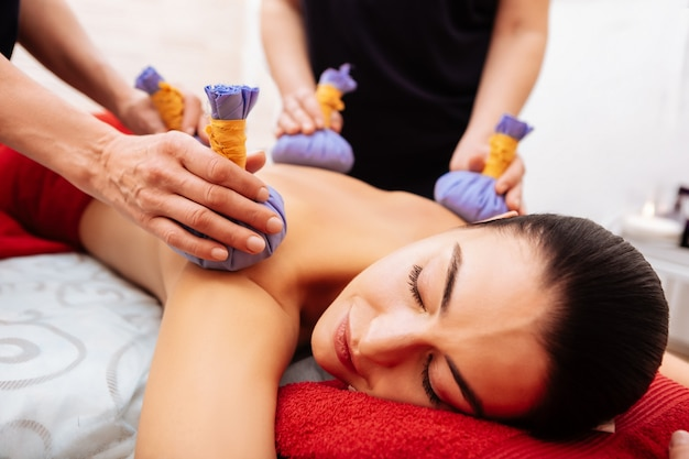 Extraordinary massage. pleasant woman enjoying gentle treatment while masters stroking her naked body in spa cabinet