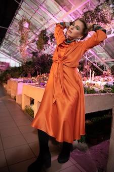 派手なファッション。写真撮影に参加しながら手を挙げている魅力的な愉快な女性