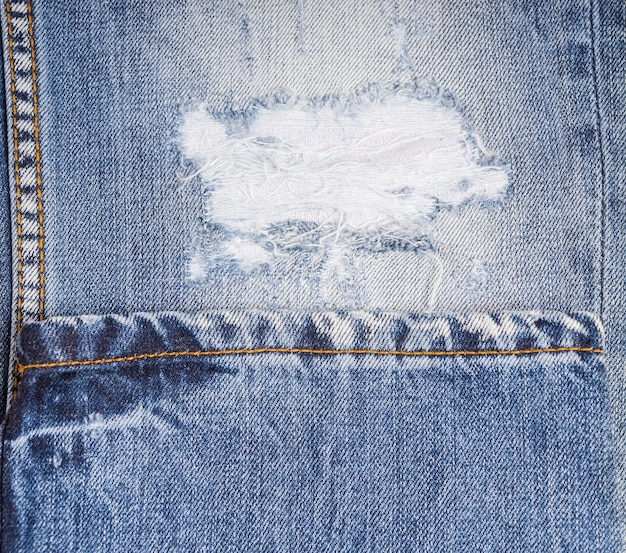 Extreme close up of distressed blue jeans - detail of frayed rip in faded demin pant leg folded with hem