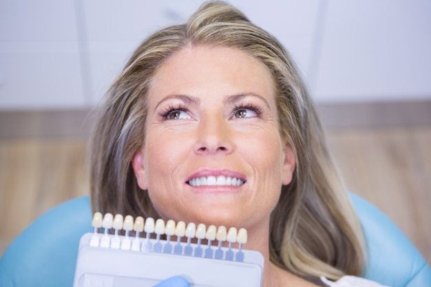 Extreme close up doctor holding tooth whitening equipment by smiling patient