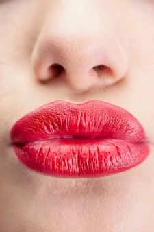 Extreme close up on gorgeous red lips kissing at camera