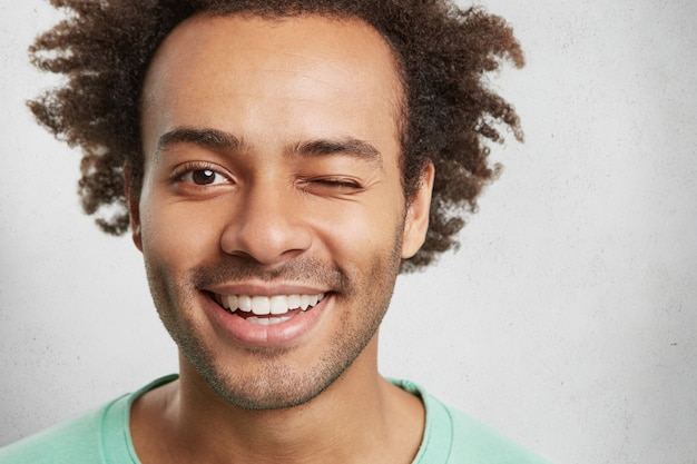 Extreme close up of mixed race handsome man has trendy hairdo, smiles pleasantly and blinks eye