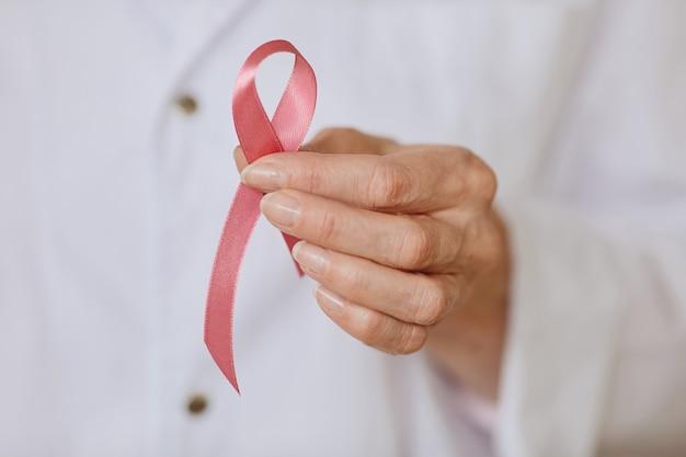 유방암 인식, 복사 공간의 상징으로 흰색 실험실 코트에 핑크 리본을 들고 인식 할 수없는 여성 의사의 극단적 인 가까이