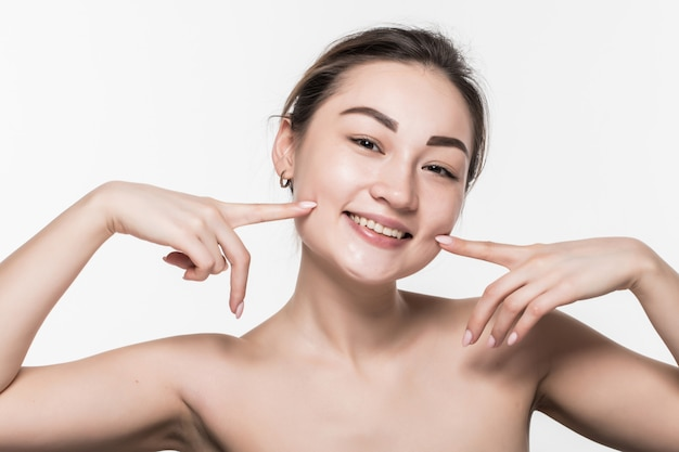 Extreme close up portrait of cute young asian woman pointing at wrinkles below cheek. girl with charming smile and healthy white teeth isolated on white wall.