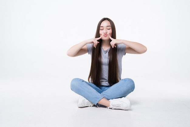 Чрезвычайно крупным планом портрет милой молодой женщины, указывая на морщины под щекой, сидя на полу, изолированном на белой стене.