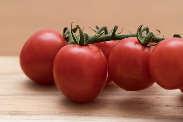 Extreme close up of red ripe organic tomatoes on branch on wooden board