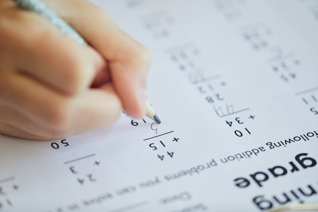 Extreme close up of unrecognizable child doing math test for online school while studying at home, copy space