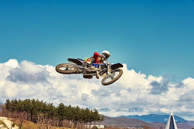 Extreme concept challenge yourself extreme jump on a motorcycle on a background of blue sky with clouds copy space all or nothing