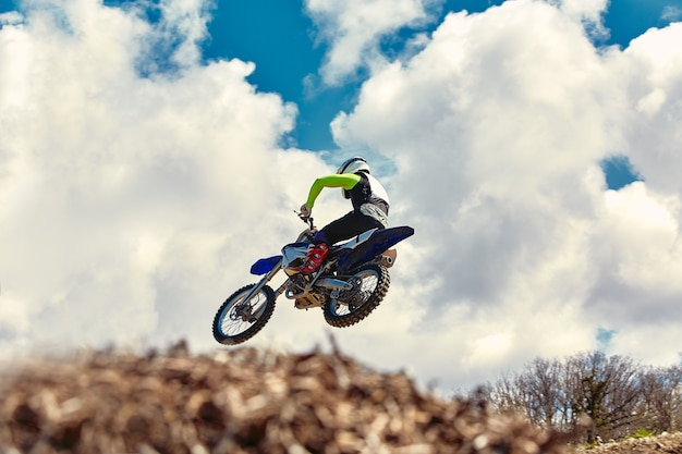 Extreme concept, challenge yourself. extreme jump on a motorcycle with blue sky with clouds. copy space, all or nothing.