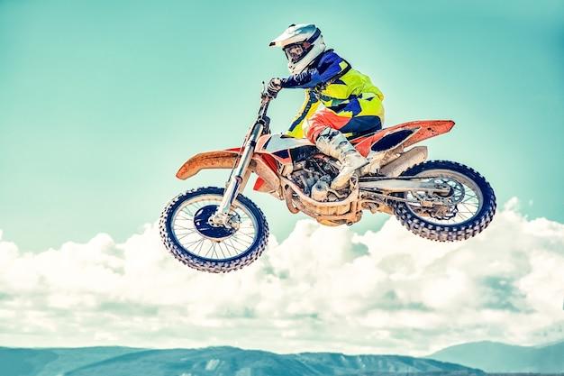 Экстремальная концепция, бросьте вызов самому себе. экстремальный прыжок на мотоцикле на фоне голубого неба с облаками. скопируйте пространство, все или ничего.