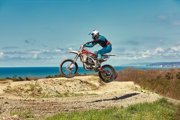 Экстремальная концепция, вызовите себе экстремальный прыжок на мотоцикле над голубым небом с облаками