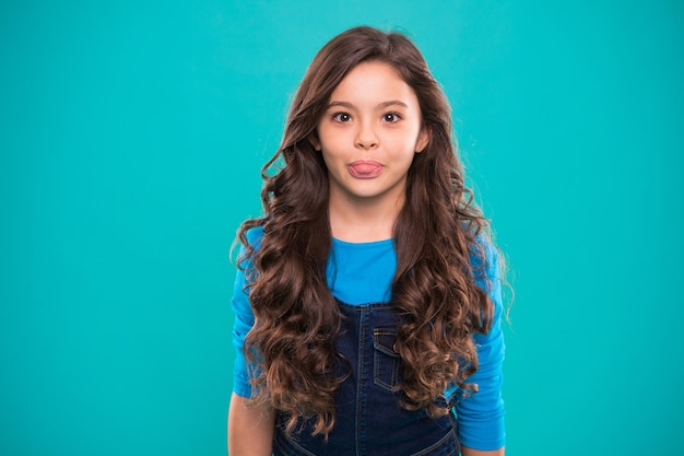 Extreme hair volume. kid girl long healthy shiny hair. kid happy cute face with adorable curly hairstyle stand over blue background. teaching healthy hair care habits. little girl grow long hair.