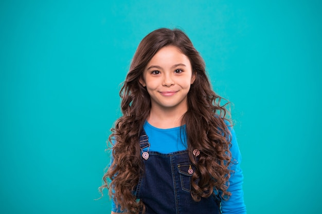 Extreme hair volume. kid girl long healthy shiny hair. little girl grow long hair. teaching healthy hair care habits. kid happy cute face with adorable curly hairstyle stand over blue background.