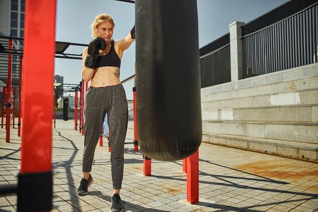 魅力的なスポーティーな女性の極端なロングショットは、スポーツグラウンドでのkikcboxingトレーニング中に左ボクシンググローブでパンチしています