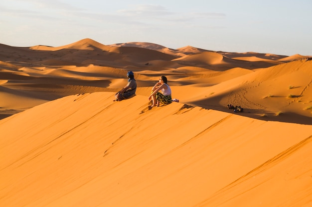 Extreme long shot of two people sitting on top of dune