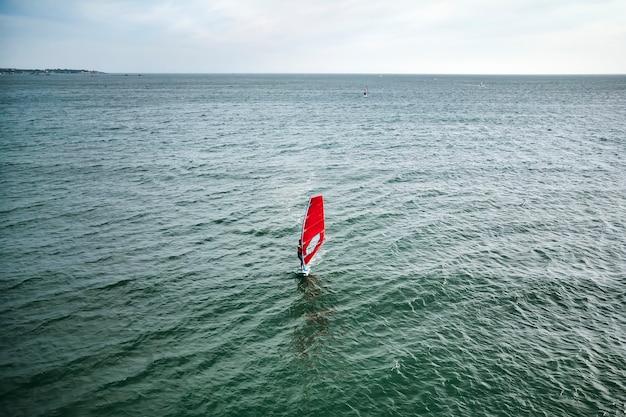 エクストリームマンアスリートは、青い海と地平線に逆らって海の波でウィンドサーフィンをします。エクストリームウォータースポーツ。水上での赤い帆の動き。海での夏の楽しみ。