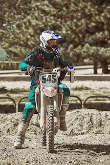 Экстремальные мотогонки. байкер готовится к бездорожью, на мотоцикле к экстремальным гонкам.