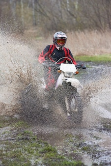 Extreme racing on mud track where skilled man riding in puddle